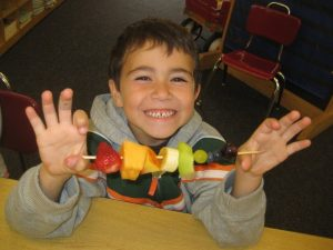 Boy enjoying his fruit kabab at school